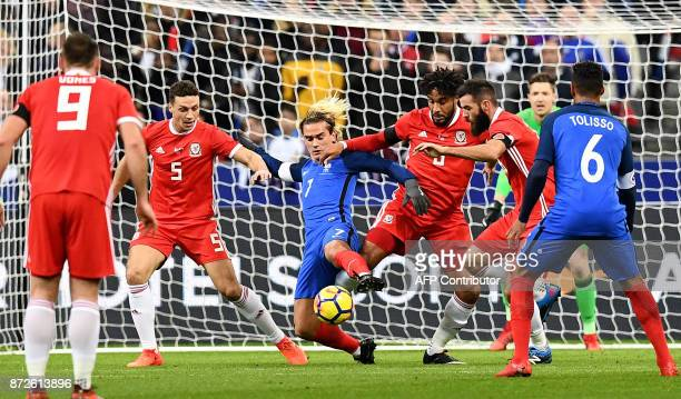 France's forward Antoine Griezmann vies for the ball with Wales team players by the goal during the friendly football match between France and Wales...