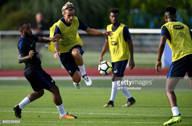 France's forward Antoine Griezmann vies with forward Alexandre Lacazette during a training session in Clairefontaine en Yvelines on August 28 as part...