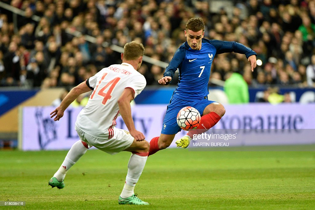 TOPSHOT - France's forward Antoine Griezmann (R) vies with Russia's defender Vasili Berezutski during the international friendly football match between France and Russia at the Stade de France in Saint-Denis, north of Paris, on March 29, 2016.