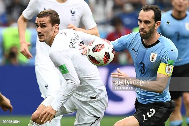 TOPSHOT France's forward Antoine Griezmann vies with Uruguay's defender Diego Godin during the Russia 2018 World Cup quarterfinal football match...
