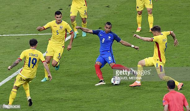 France's forward Dimitri Payet aims to score a goal past Romania's forward Bogdan Stancu and Romania's midfielder Ovidiu Hoban and Romania's...