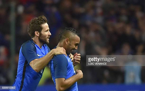 France's forward Dimitri Payet celebrates with his teammates midfielder Yohan Cabaye after scoring a goal during the International friendly football...