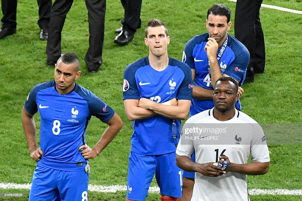 France's forward Dimitri Payet, France's midfielder Morgan Schneiderlin, France's defender Adil Rami and France's goalkeeper Steve Mandanda react after their team's defeat in the Euro 2016 final football match between Portugal and France at the Stade de France in Saint-Denis, north of Paris, on July 10, 2016. / AFP / PHILIPPE