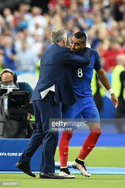 France's forward Dimitri Payet is congratulated by France's coach Didier Deschamps after scoring the 2-1 during the Euro 2016 group A football match...