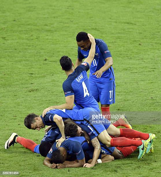 France's forward Dimitri Payet is congratulated by team mates after scoring the 2-1 goal during the Euro 2016 group A football match between France...