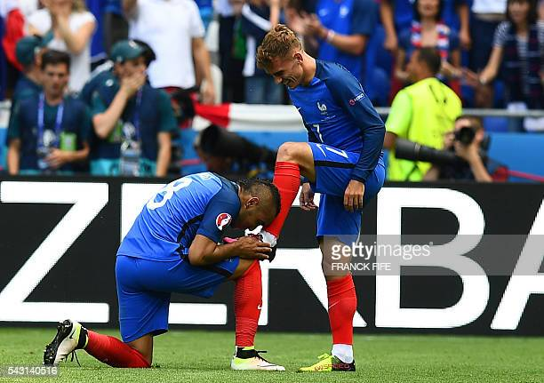 France's forward Dimitri Payet kisses the shoe of France's forward Antoine Griezmann after he scored during the Euro 2016 round of 16 football match...