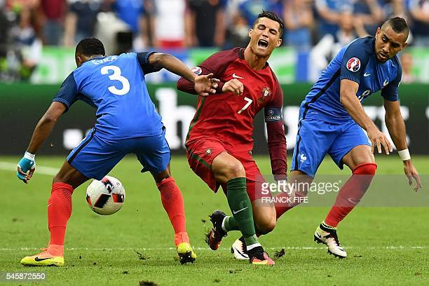 TOPSHOT France's forward Dimitri Payet looks on as Portugal's forward Cristiano Ronaldo falls onto the pitch during the Euro 2016 final football...