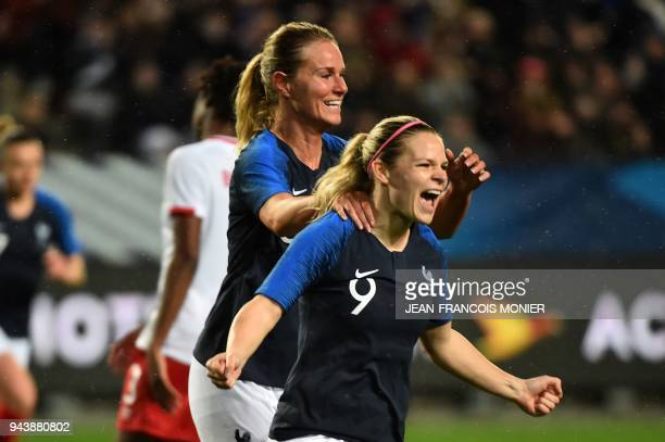 France's forward Eugenie Le Sommer is congratulated after scoring by teammate midfielder Amandine Henry during the friendly womens football match...