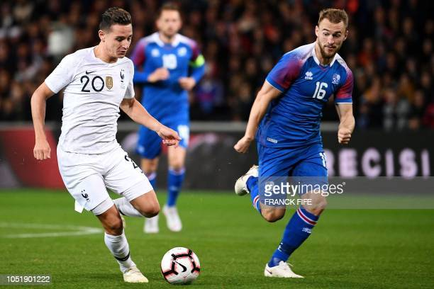 France's forward Florian Thauvin vies with Iceland's midfielder Runar Mar Sigurjonsson during the friendly football match between France and Iceland...