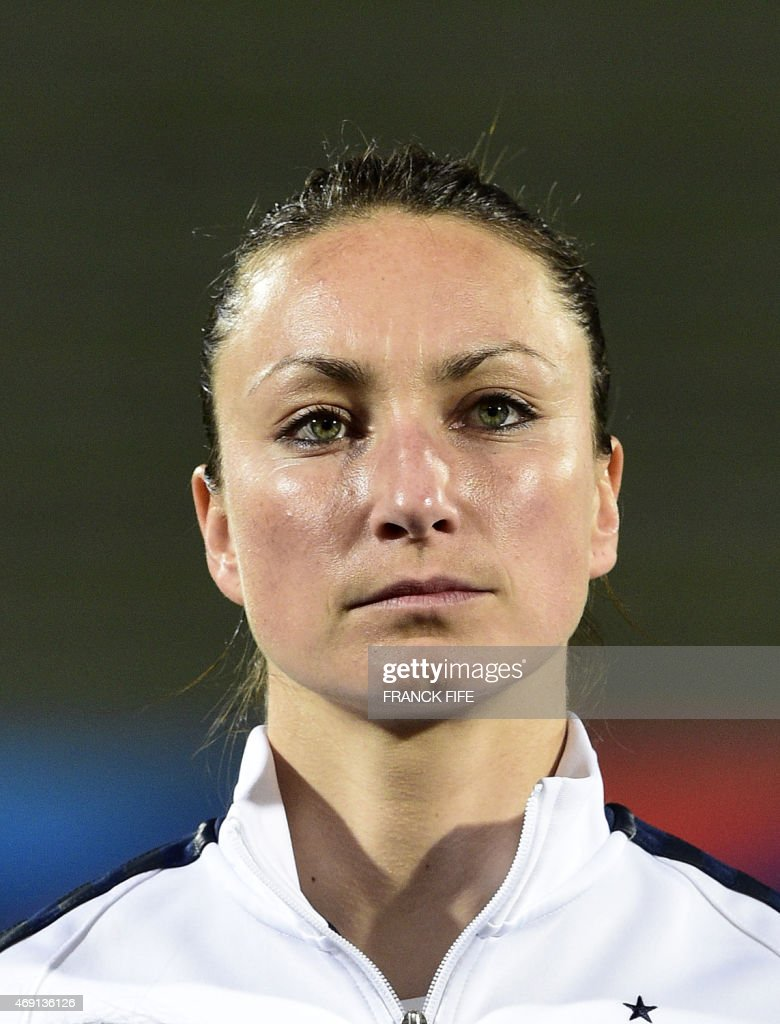 France's forward Gaetane Thiney poses during the French national anthem during the friendly football match France vs Canada, on April 9, 2015 at the Stade Robert-Bobin stadium in Bondoufle, near Paris.