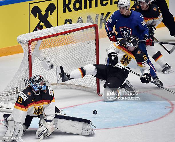 France's forward Jordann Perret vies with Germany's defender Christian Ehrhoff in front of the net of Germany's goalie Timo Pielmeier during the...