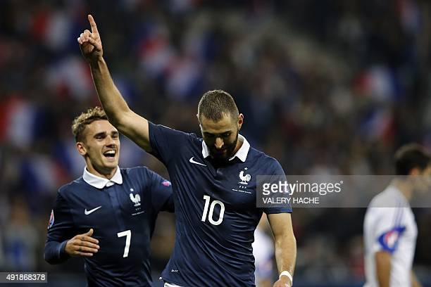 France's forward Karim Benzema celebrates with France's forward Antoine Griezmann after scoring a goal during the friendly football match between...