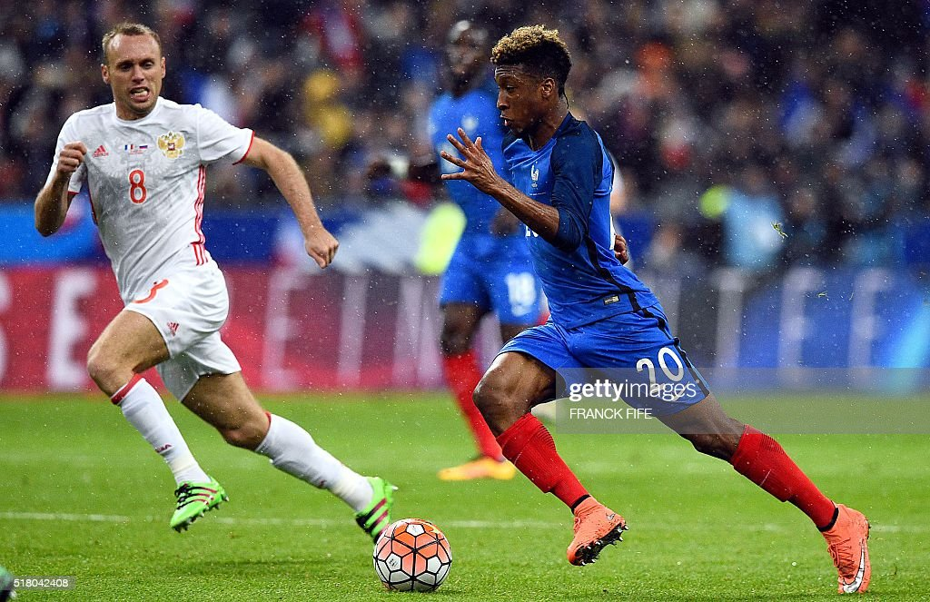 France's forward Kingsley Coman (R) vies for the ball with Russia's Denis Glushakov during the international friendly football match between France and Russia at the Stade de France in Saint-Denis, north of Paris, on March 29, 2016.