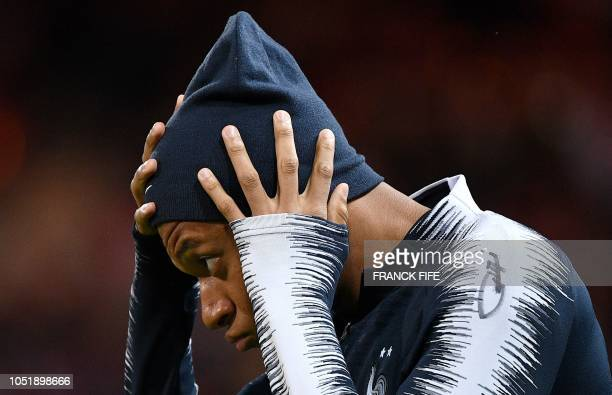 France's forward Kylian Mbappe adjusts his hat as he warms up ahead of the friendly football match between France and Iceland at the Roudourou...