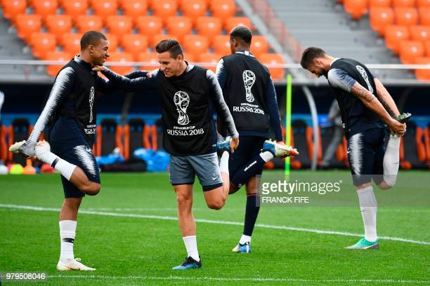 France's forward Kylian Mbappe and France's forward Florian Thauvin stretch during a training session at the Ekaterinburg Arena in Ekaterinburg on...