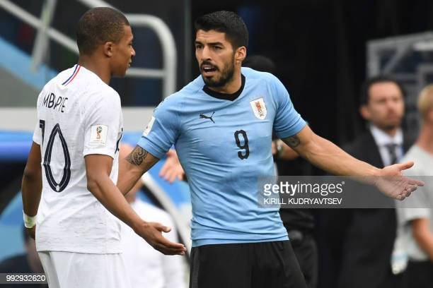 TOPSHOT France's forward Kylian Mbappe argues with Uruguay's forward Luis Suarez during the Russia 2018 World Cup quarterfinal football match between...
