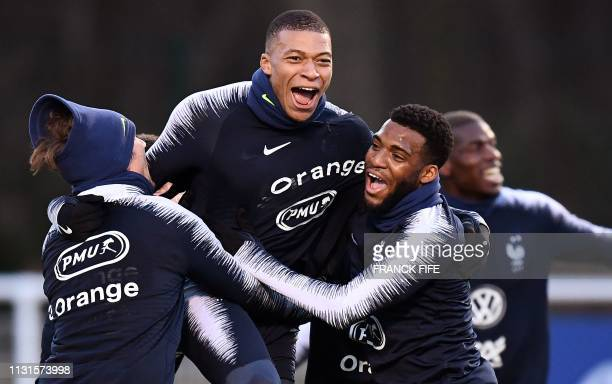 TOPSHOT France's forward Kylian Mbappe celebrates a goal with France's forward Antoine Griezmann and France's midfielder Thomas Lemar during a...