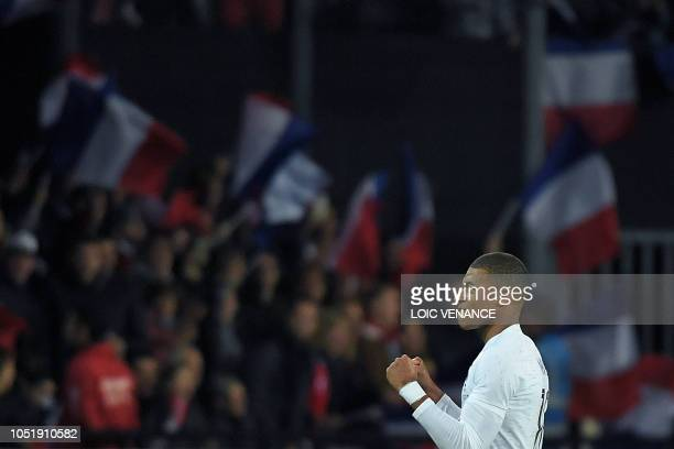 TOPSHOT France's forward Kylian Mbappe celebrates after scoring a penalty kick during the friendly football match between France and Iceland at the...