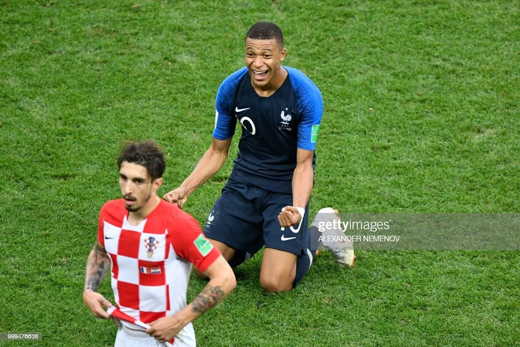 France's forward Kylian Mbappe (R) celebrates next to Croatia's defender Sime Vrsaljko (front) after winning at the end the Russia 2018 World Cup final football match between France and Croatia at the Luzhniki Stadium in Moscow on July 15, 2018. (Photo by Alexander NEMENOV / AFP) / RESTRICTED