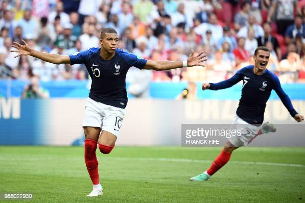 TOPSHOT France's forward Kylian Mbappe celebrates past France's forward Antoine Griezmann after scoring their fourth goal during the Russia 2018...