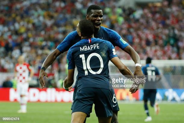 TOPSHOT France's forward Kylian Mbappe celebrates scoring the 41 goal with France's midfielder Paul Pogba during the Russia 2018 World Cup final...