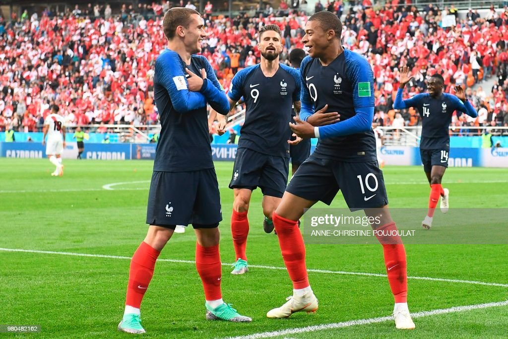TOPSHOT - France's forward Kylian Mbappe (R) celebrates scoring the opening goal with his teammates forward Antoine Griezmann (L) and forward Olivier Giroud (C) during the Russia 2018 World Cup Group C football match between France and Peru at the Ekaterinburg Arena in Ekaterinburg on June 21, 2018. (Photo by Anne-Christine POUJOULAT / AFP) / RESTRICTED