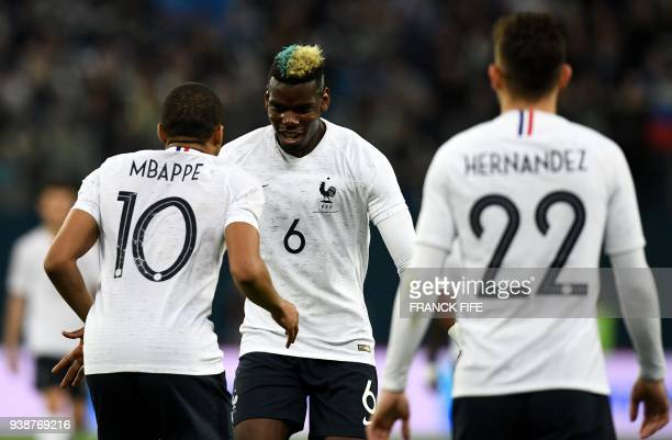 TOPSHOT France's forward Kylian Mbappe celebrates with France's midfielder Paul Pogba after scoring a goal during an international friendly football...