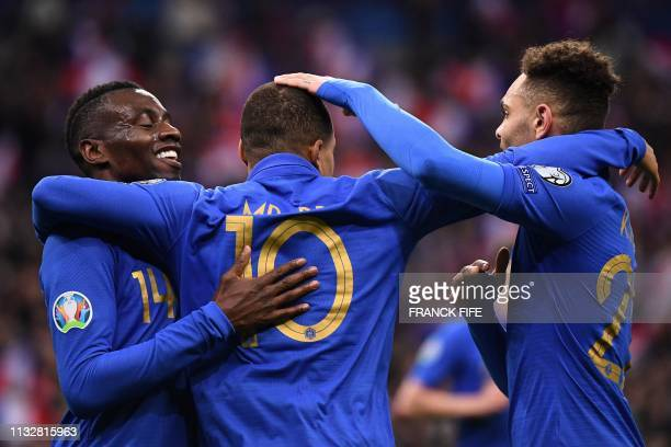 TOPSHOT France's forward Kylian Mbappe celebrates with teammates France's midfielder Blaise Matuidi AND France's defender Layvin Kurzawa after...