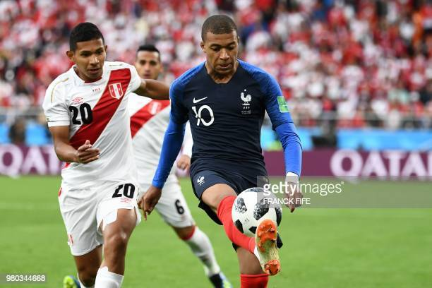 TOPSHOT France's forward Kylian Mbappe controls the ball next to Peru's midfielder Edison Flores during the Russia 2018 World Cup Group C football...