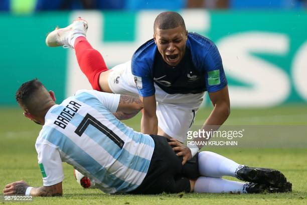 France's forward Kylian Mbappe falls over Argentina's midfielder Ever Banega during the Russia 2018 World Cup round of 16 football match between...