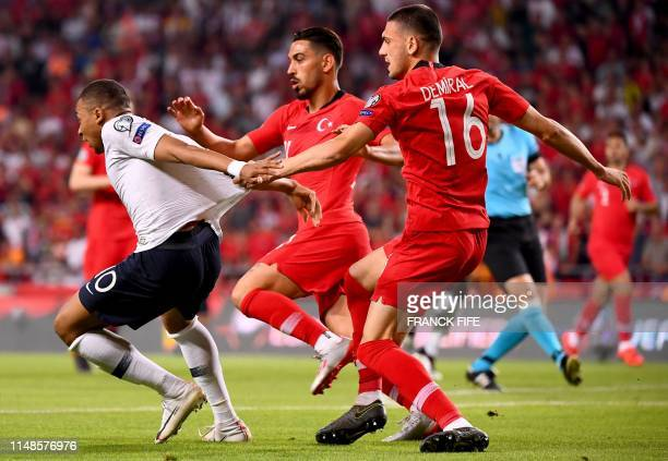 France's forward Kylian Mbappe fights for the ball with Turkey's defender Merih Demiral and Turkey's midfielder Irfan Kahveci during the Euro 2020...
