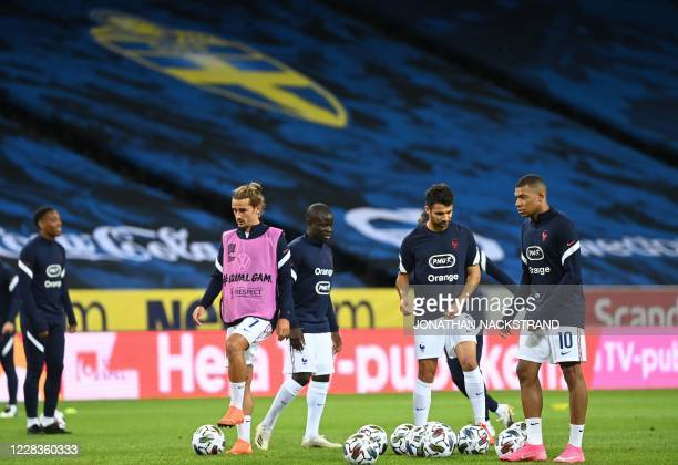 France's forward Kylian Mbappe France's defender Leo Dubois France's midfielder N'Golo Kante and France's forward Antoine Griezmann warm up prior to...