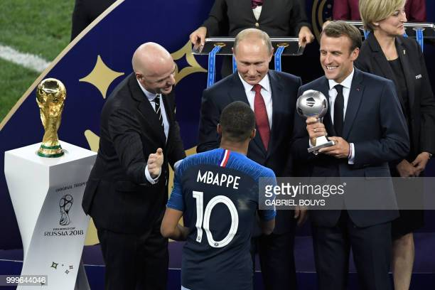 France's forward Kylian Mbappe is congratulated by FIFA president Gianni Infantino , Russian President Vladimir Putin and French President Emmanuel...