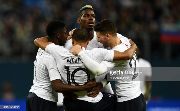 TOPSHOT France's forward Kylian Mbappe is congratulated by teammates after scoring a goal during an international friendly football match between...
