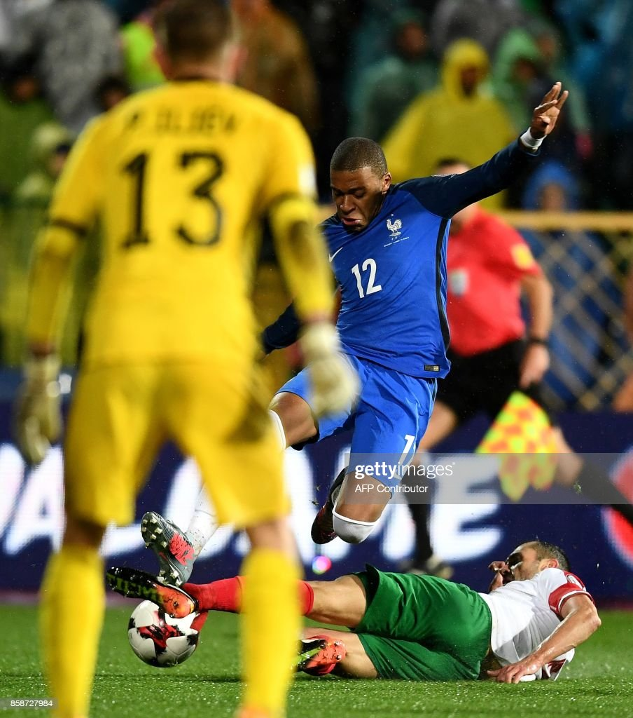 France's forward Kylian Mbappe (C) is tackled by Bulgaria's defender Petar Zanev (R) as Bulgaria's goalkeeper Plamen IIiev (L) looks on during the FIFA World Cup 2018 qualifying football match between Bulgaria and France at The Vasil Levski Stadium in Sofia on October 7, 2017. /