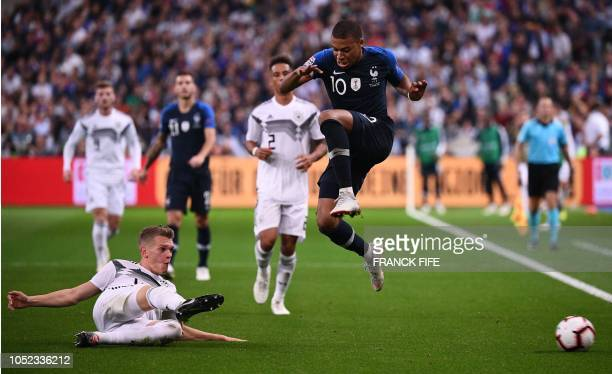 France's forward Kylian Mbappe is tackled by German's defender Matthias Ginter during the UEFA Nations League football match between France and...