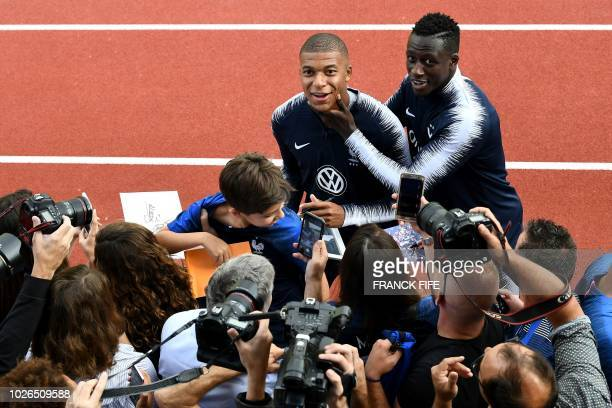 TOPSHOT France's forward Kylian Mbappe jokes with France's defender Benjamin Mendy as they are greeted by fans ahead of a training session in...
