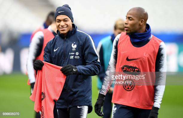 France's forward Kylian Mbappe jokes with France's defender Djibril Sidibe during a training session at the Stade de France in Saint-Denis, north of...