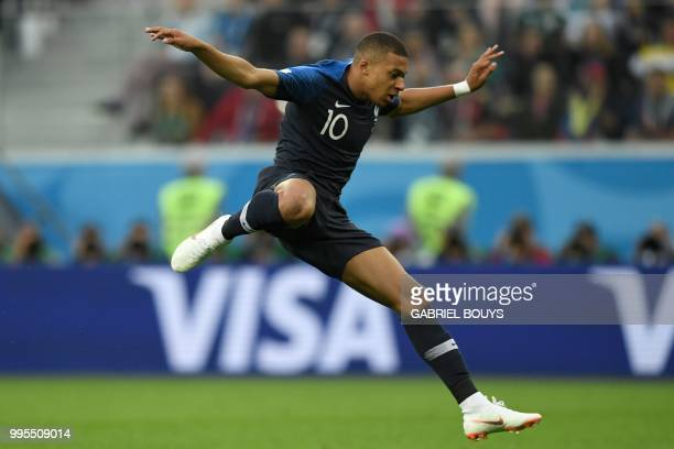 France's forward Kylian Mbappe jumps over the keeper during the Russia 2018 World Cup semifinal football match between France and Belgium at the...