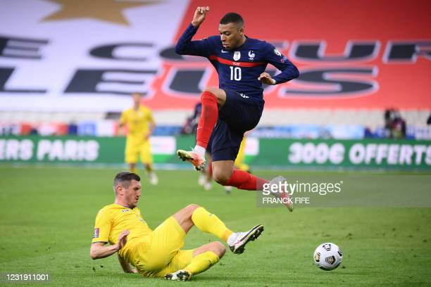 France's forward Kylian Mbappe jumps to avoid a tackle during the FIFA World Cup Qatar 2022 qualification football match between France and Ukraine...
