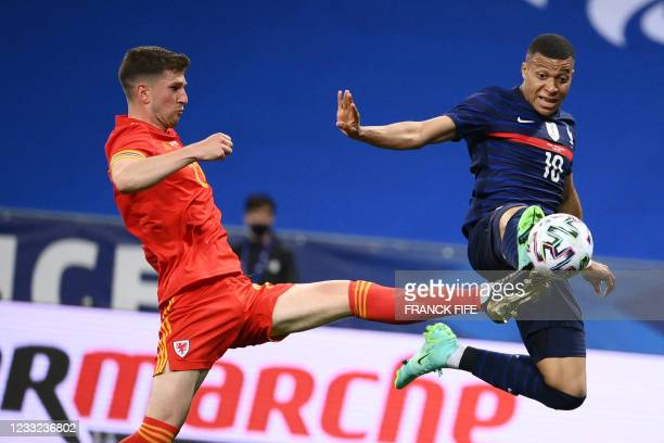 France's forward Kylian Mbappe kicks the ball past Wales' defender Chris Mepham to score the opener during the friendly football match between France...