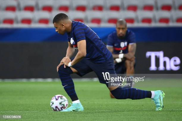 France's forward Kylian Mbappe kneels against racism before the friendly football match between France and Wales at the Allianz Riviera Stadium in...