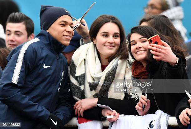 TOPSHOT France's forward Kylian Mbappe poses with a fans before a training session in ClairefontaineenYvelines southwest of Paris on March 19 as part...