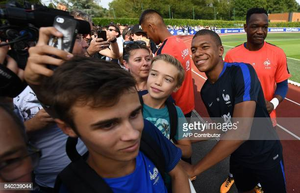 France's forward Kylian Mbappe poses with fans before a training session in Clairefontaine en Yvelines on August 28 as part of the team's preparation...