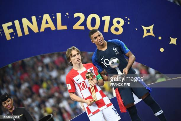 France's forward Kylian Mbappe poses with the FIFA Young Player award beside Croatia's midfielder Luka Modric holding the adidas Golden Ball prize...