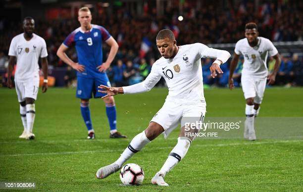 TOPSHOT France's forward Kylian Mbappe shoots to score from the penalty spot during the friendly football match between France and Iceland at the...