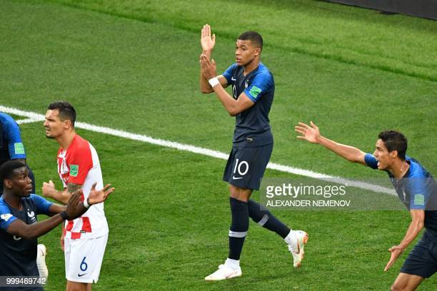 TOPSHOT France's forward Kylian Mbappe shows his arm to Argentinian referee Nestor Pitana in order appeal for a hand ball during the Russia 2018...