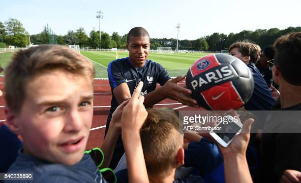 France's forward Kylian Mbappe signs autographs before a training session in Clairefontaine en Yvelines on August 28 as part of the team's...
