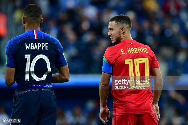 France's forward Kylian Mbappe speaks with Belgium's forward Eden Hazard during the Russia 2018 World Cup semi-final football match between France...