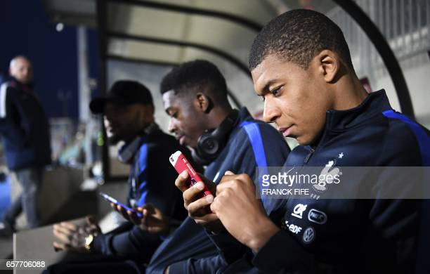 France's forward Kylian Mbappe uses a mobile phone on the bench next to France's forward Ousmane Dembele and France's defender Layvin Kurzawa before...